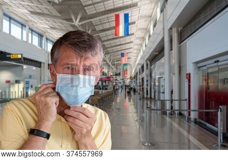 Senior Man Or Traveler Adjusting Face Mask In Airport Terminal And Looking Afraid Of Travel With Cor