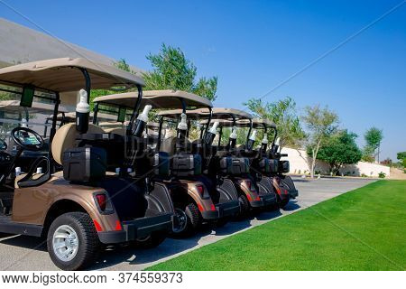 Background Image Of Golf Carts Parked On A Golf Closure In A Line.golf Course