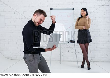 A Smiling Businessman Is Standing With A Laptop While A Woman Is Writing A Business Plan On A White
