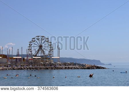 Liguria, Italy - Summer 2020: Tourists Bathe In The Sea In A Ligurian Bay, In The Background A Ferri