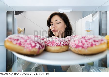Confused Woman Thinking Looking At Sweets In Fridge Or Refrigerator
