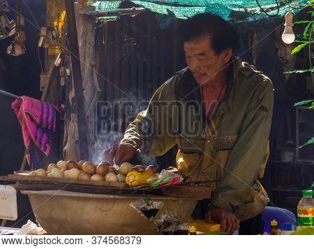 Thong Pha Phum, Thailand - January 4, 2020: Man Selling Traditional Food Near The Hin Dat Hot Spring
