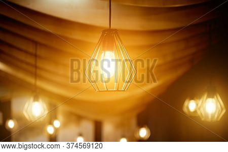 Ceiling Lamps Made Of Rebar Under A Curved Wooden Ceiling