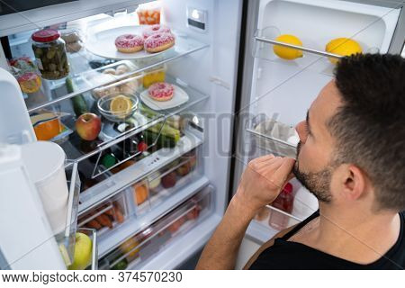 Hungry Confused Man Looking In Open Fridge In Kitchen