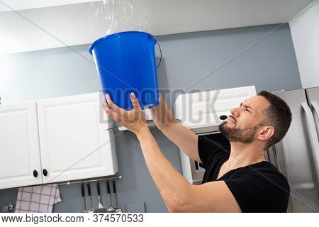 Worried Man Holding Bucket While Water Droplets Leak From Ceiling In Kitchen