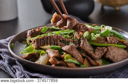 eating chinese beef and snowpeas stirfry on plate with chopsticks
