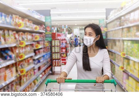 Asian Woman Wear Face Mask Push Shopping Cart In Supermarket Department Store. Girl Looking Grocery