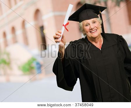 Senior Woman Holding Degree In Hand, Outdoors