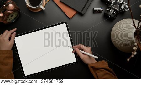 Female Worker Using Blank Screen Tablet With Stylus On Dark Luxury Office Desk With Camera, Supplies