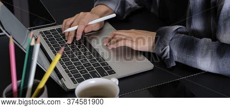 Female Hands Typing On Laptop Keyboard On Modern Office Desk With Stationery And Coffee Cup