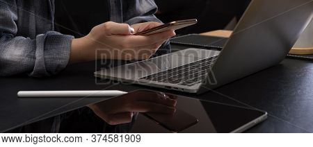 Female Worker Using Smartphone While Working At Modern Office Desk