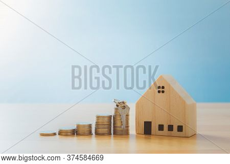 Key Placed Front Of Stack Coins With Model House. Model House With Key House Concept For Property La
