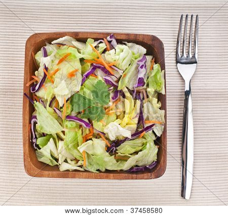Mixed fresh vegetable salad in bamboo dish with fork on napkin  background
