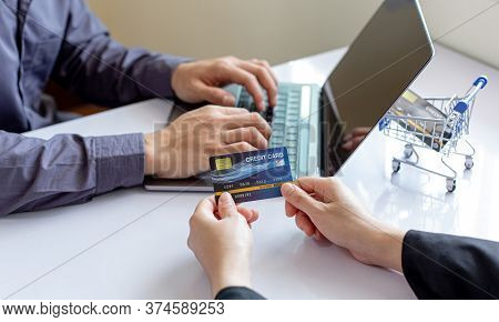 Both business people use laptop and phones to register online purchases using credit card payments,
