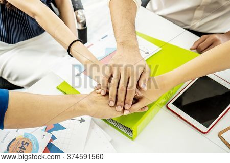 Business Team Stack Hands Support Concept. Four Business People In Formal Wear Sitting And Discussin