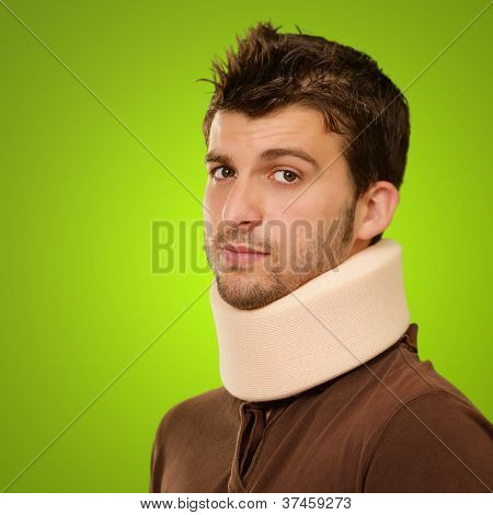 Young Man Wearing Cervical Collar Isolated On Green Background