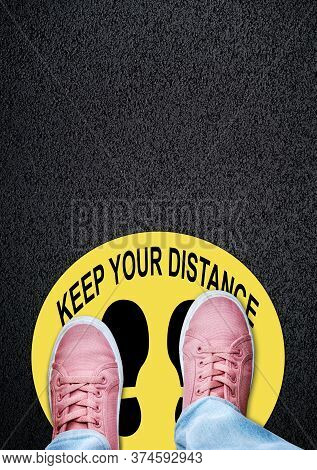 Person Standing On A Keep Your Distance Sticker On Asphalt Ground With Copy Space. Concept Of Physic