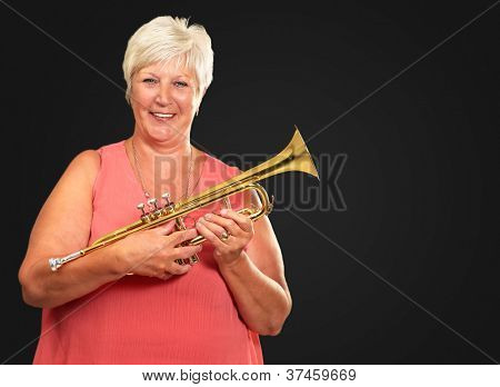 Mature Woman Blowing Her Trumpet Isolated On Black Background