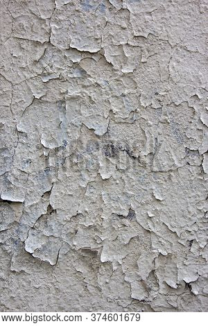 Cracked Flaking White Paint On Old Stone Wall. Old Weathered Painted White Plastered Peeled Wall Bac