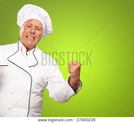 Portrait Of Angry Chef On Green Background