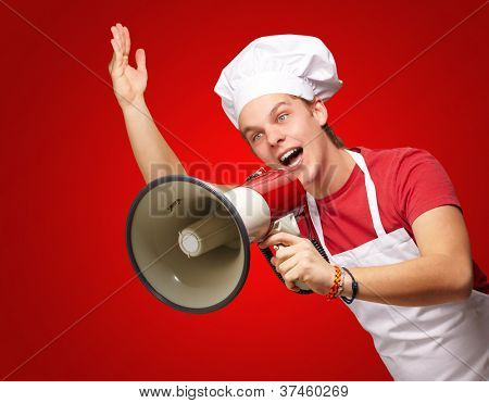 portrait of young cook man shouting with megaphone over red background poster