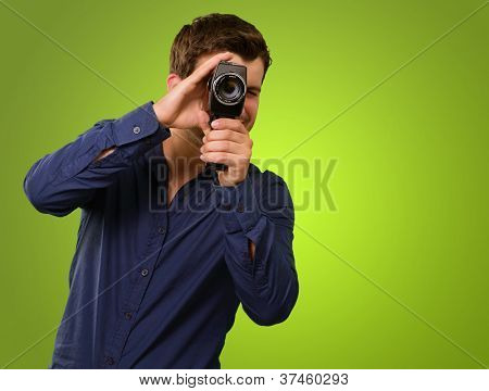 Young Man Holding Old Camera On Green Background