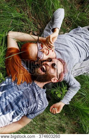 Joyful Couple, Seated Down On A Green Grass, In Park, Seated Down With Turned Heads, In Sunglasses,