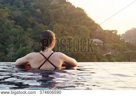 Pretty Brunette In Outdoor Swimming Pool Against Forestry Hills Sunlight Closeup Copy Space