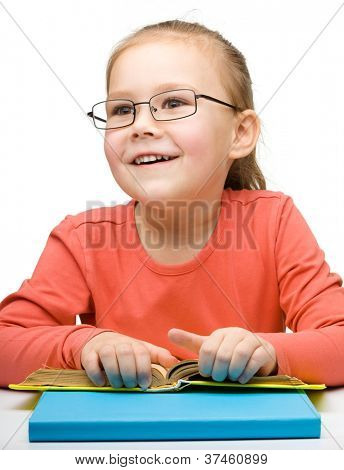 Cute cheerful little girl reading book while wearing glasses, isolated over white