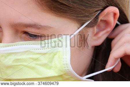 Young Girl Correctly Wears Mask With Elastic Band Behind Ear To Protect Herself From Infections