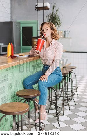Nice Young Lady In Shirt And Jeans Sitting At The Bar Counter And Drinking Soda Water While Dreamily