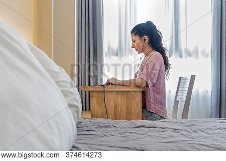 View From Behind The Bed At A Smiling Woman Working At A Laptop In Headphones.  Always In Touch. Hom