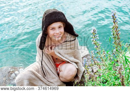Happy Laughing Emotional Boy In Winter Hat With Earflaps Sunbathes On A Lake In Summer. Beach Holida