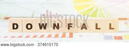 Word Downfall Made With Letters On Wooden Cubes On Desk With Different Color Graphs And Diagram At L