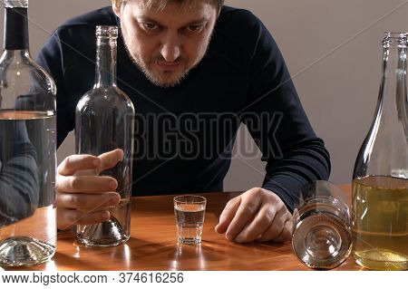A Man In Alcoholic Intoxication Holds A Glass Of Alcohol. Alcoholism, Addiction, Delirium.