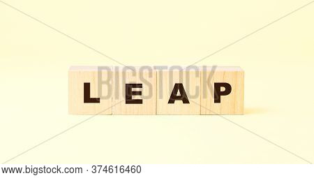 Word Leap Written With Black Letters On Small Wooden Blocks Against Bright Yellow Background At Ligh