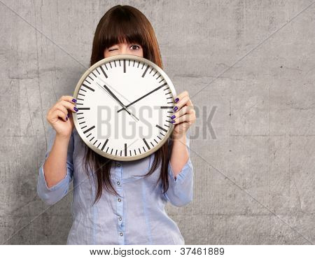 Woman Holding Clock Winking, Indoor