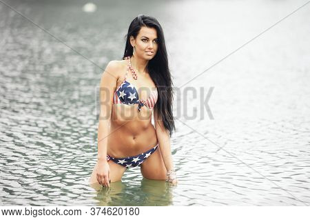 Cheerful Woman Celebrating Us Independence Day On The Beach With American Flag