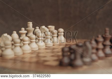 Chess Board And Chess Pieces, Wooden Small Chess Pieces On A Chess Board. Stand In Starting Position