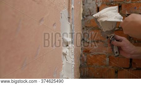 Worker Puts Putty On The Tool. Close-up Of A Womans Hand With A Metal Spatula For Applying Stucco On