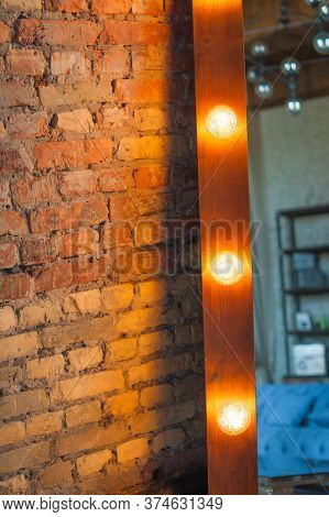 A Large Mirror In A Wooden Frame With Bulbs Near A Brick Wall