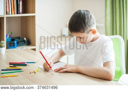 Picture Of A Thoughtful Caucasian Schoolboy In A White T-shirt Sitting On A Table Indoors, Concentra