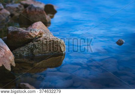 Natural Stones On The Shore Of A Lake At Dusk. Tranquil Scene, Relaxing Calm, Zen Meditation Backgro