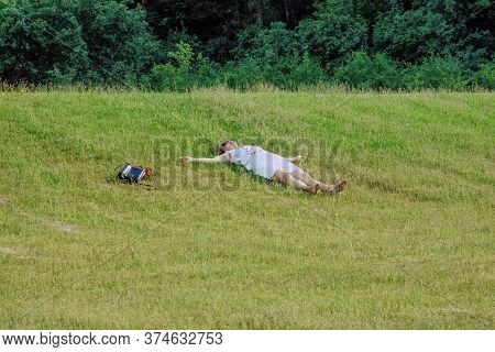 Moscow 08/06/2019 Woman In White Skirt And T-shirt With Red Hearts Lying On Grass In City Park With