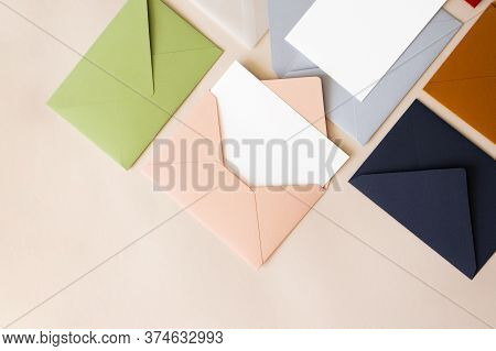 Close-up Colorful Mail Envelopes On Beige Background Flat Lay With Copy Space, Top View. Mailing Con
