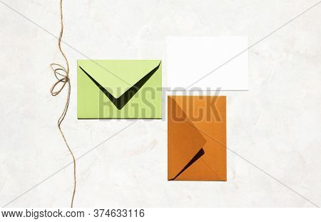 Colorful Mail Envelopes And Empty White Paper Card And Twine With Bow On Marble Stone Table, Top Vie