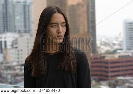Young Asian Man With Long Hair Thinking In The City Outdoors