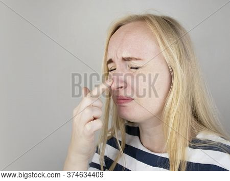 A Young Woman Touches Her Nose, Which Is Very Painful. Medical Care Concept For Difficulty Breathing
