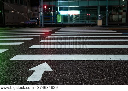 Pedestrian Crossing With Directional Arrows At Night. Pedestrian Marking On Wet Pavement. Red Signal
