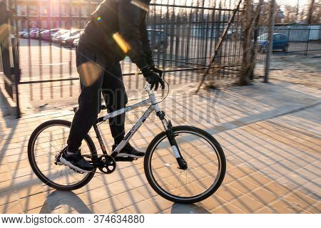 A Man In A Black Tracksuit Quickly Rides A Bicycle In Sunny Weather. A Bicycle Cyclist Rides On Pavi